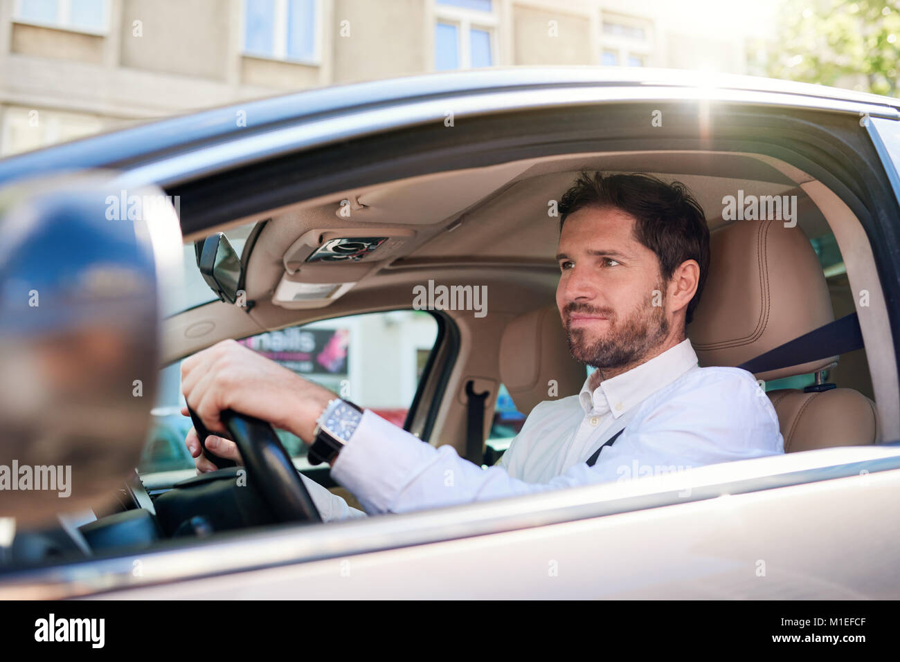 Smiling young man driving his car during his morning commute - Stock Image