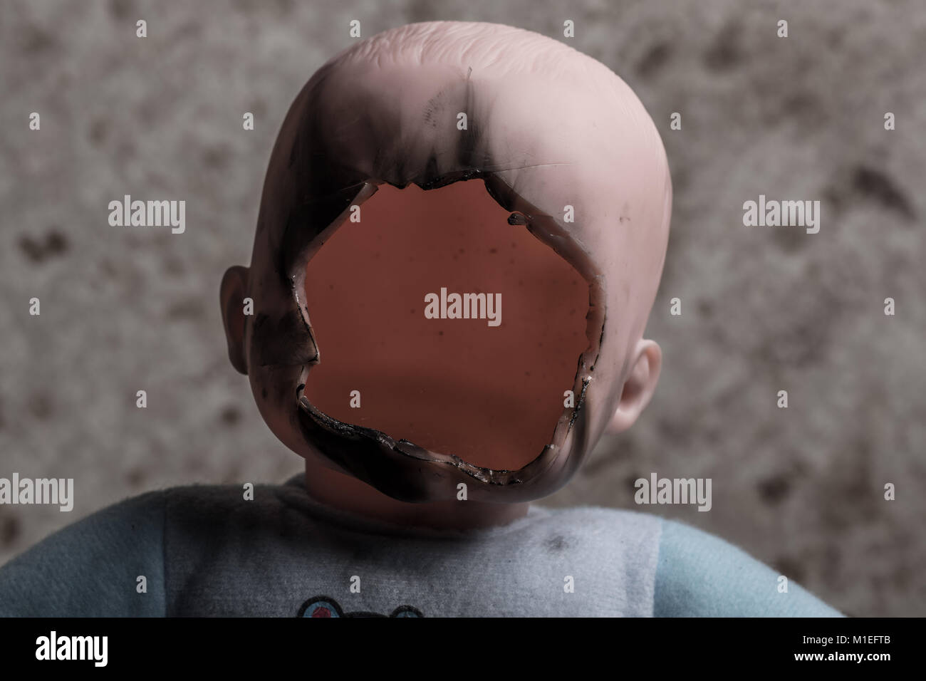 Child Doll with Its Face Cutted Off and Burned on Grunge Background - Stock Image