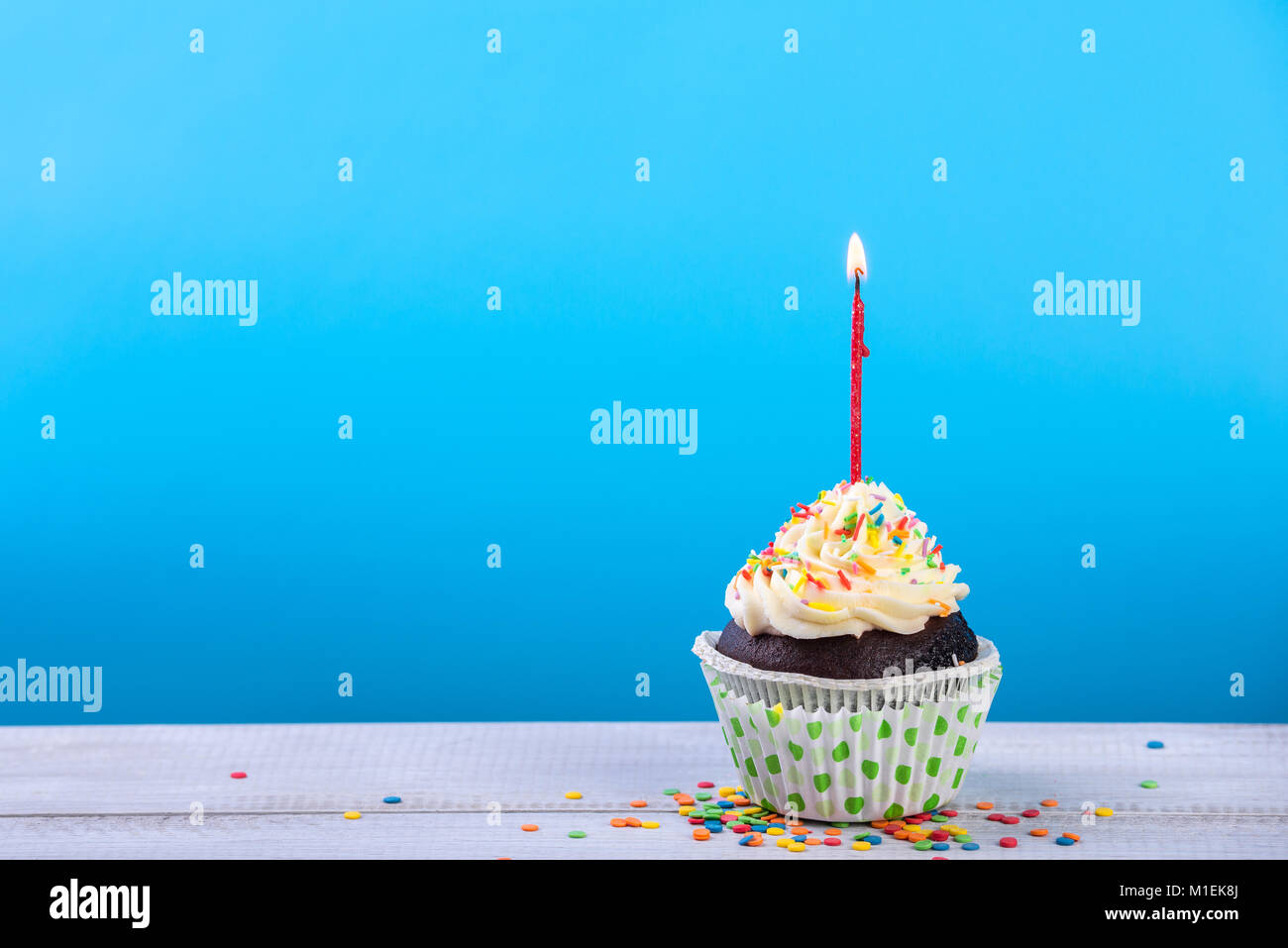 Birthday cupcake on a color background with multicolor candles. - Stock Image