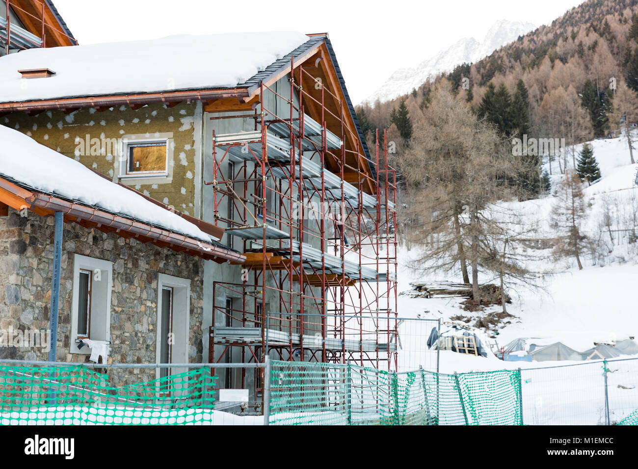 Construction of hotel or tourist apartment at ski resort in Italy, Alps - Stock Image