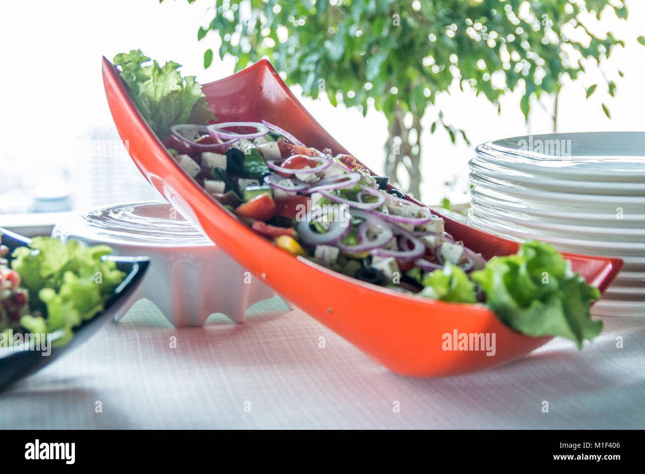 Salad with sausage, greens and other on table with white table. Catering concept. - Stock Image