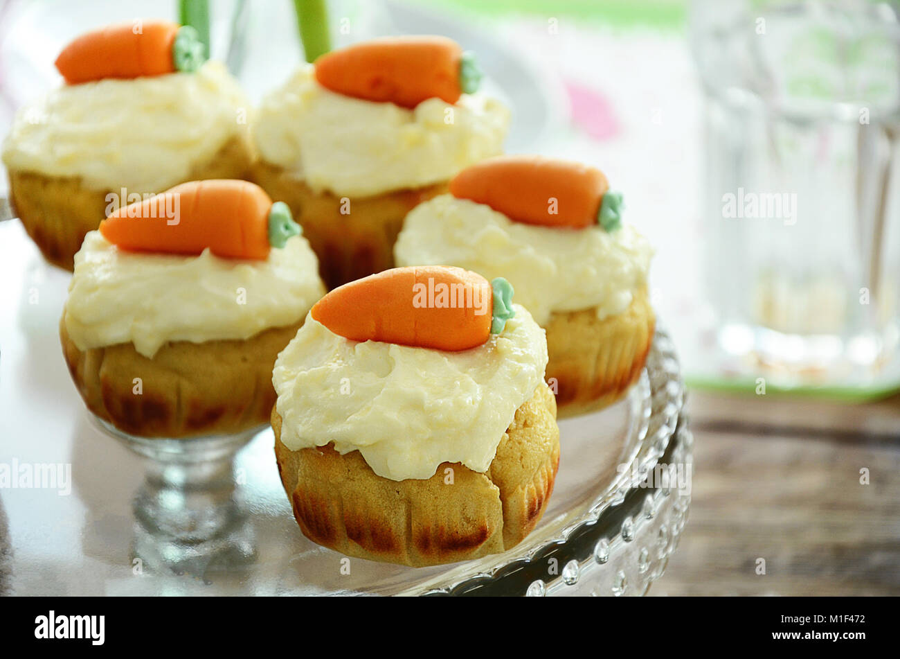 Easter cupcakes with cream cheese frosting and marzipan carrots on cake stand Stock Photo