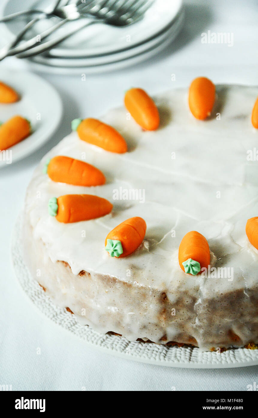 Carrot cake with marzipan carrots and white sugar glaze on white background - Stock Image