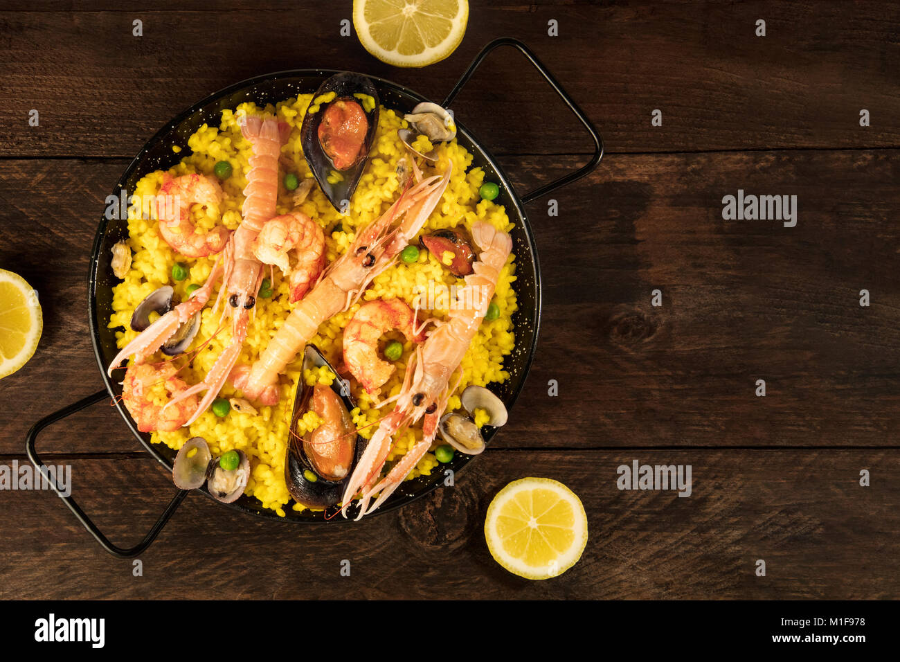 Spanish seafood paella in paellera, with lemons and copyspace - Stock Image