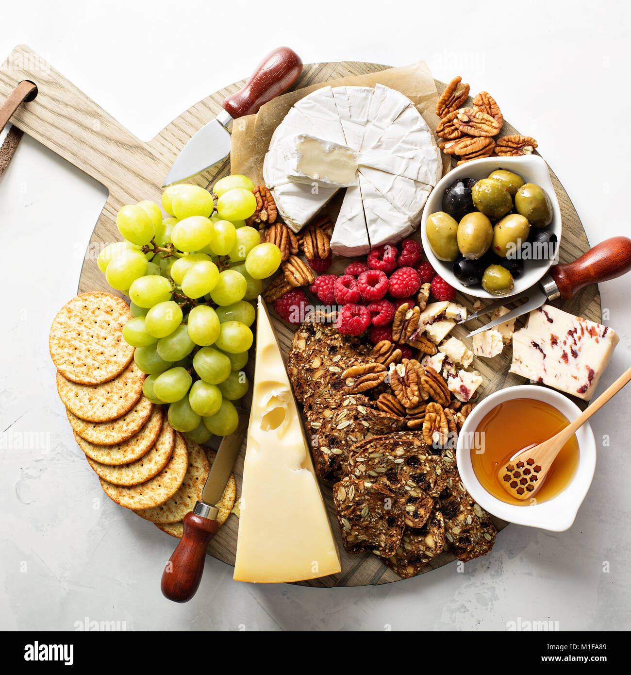 Cheese and snacks plate on white background overhead shot Stock Photo