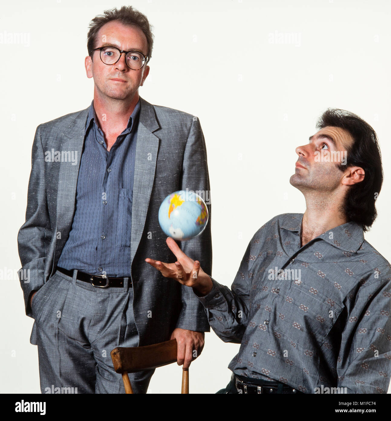Ben Mandelson, (Hijaz Mustapha), 3 mustaphas 3, throws globe in the air accompanied by another band member(Name - Stock Image