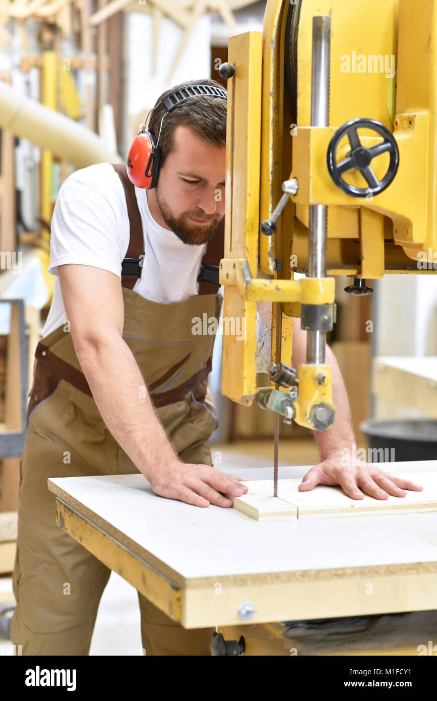 friendly carpenter with ear protectors and working clothes working on a saw in the workshop - Stock Image
