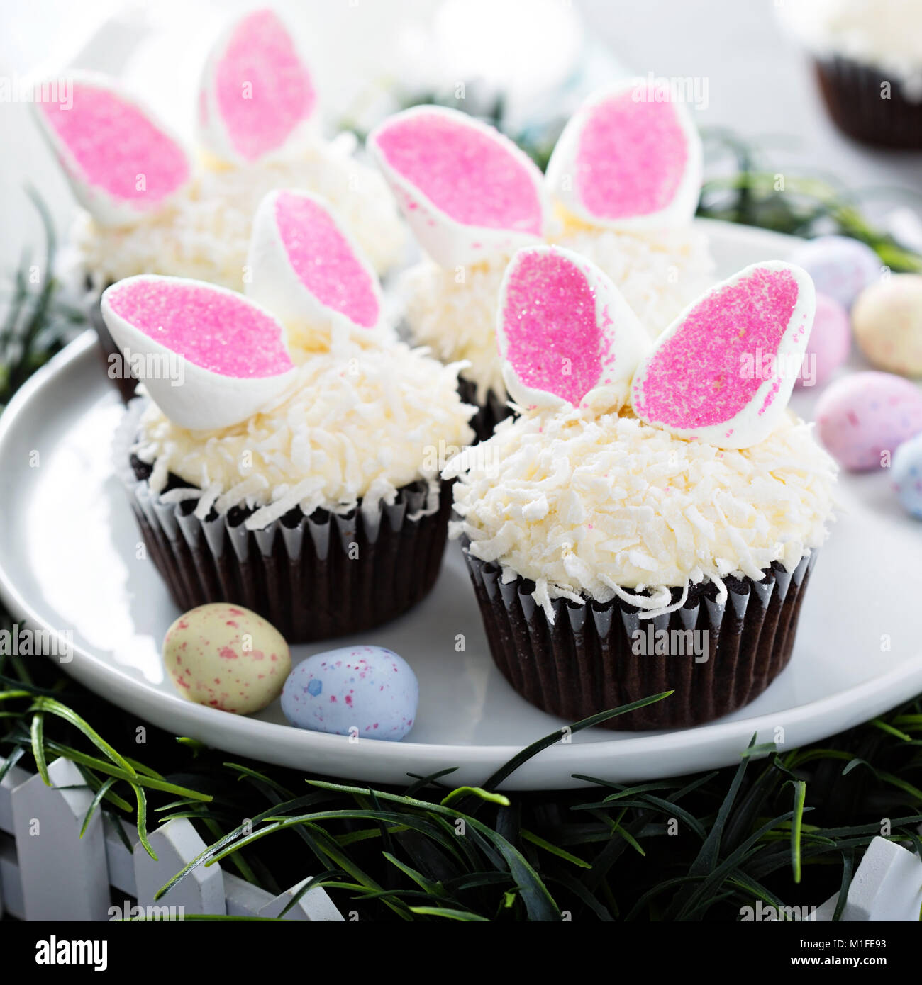 Easter chocolate cupcakes with bunny ears and coconut flakes - Stock Image