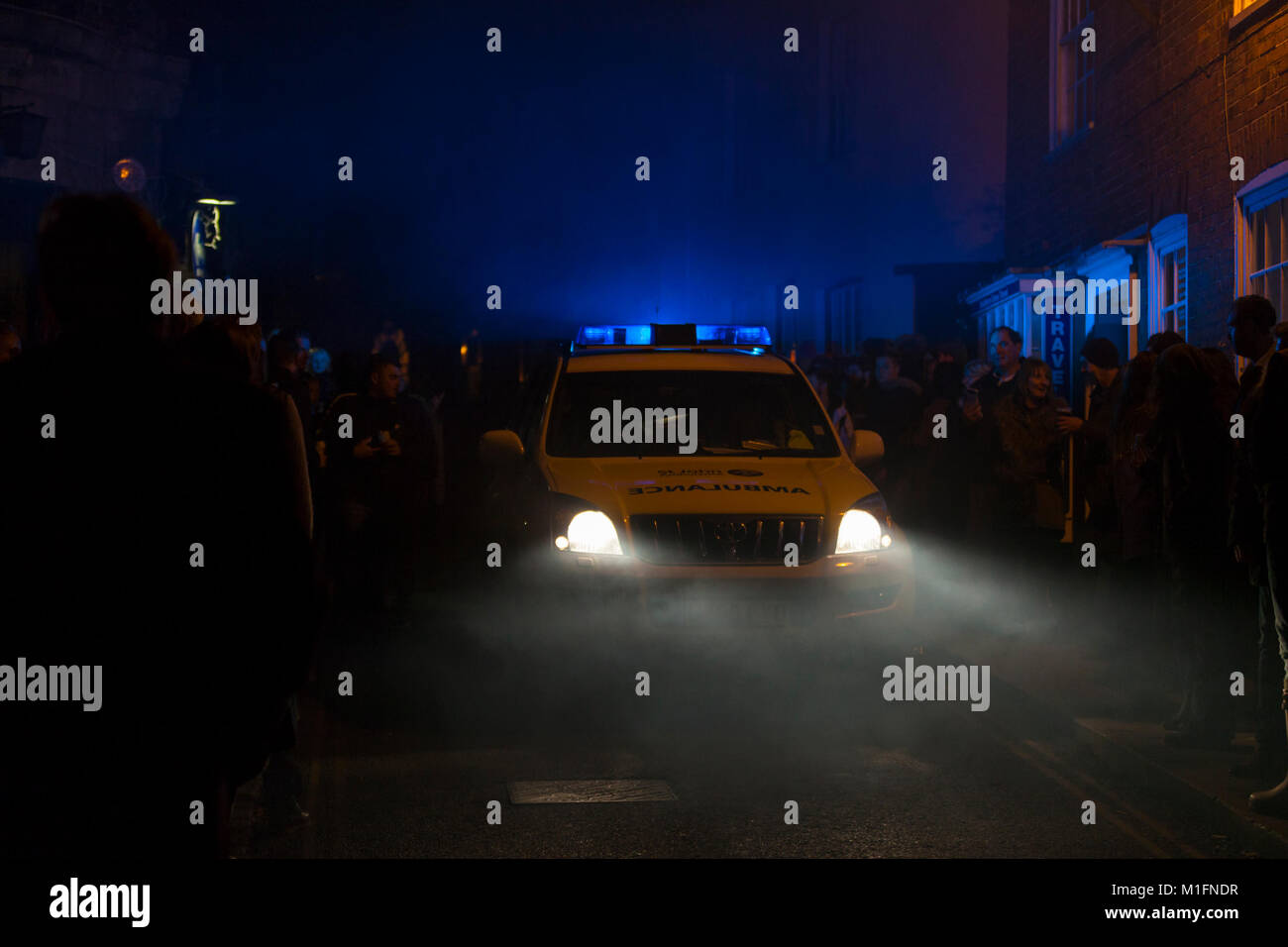 An ambulance makes its way through the crowded streets at night flashing its blue lights. Bonfire night rye 2017, - Stock Image