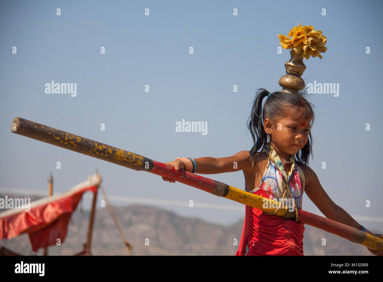 Young girl walking a tight-rope to entertain tourists at the Pushkar Camel Fair, Rajasthan, India - Stock Image