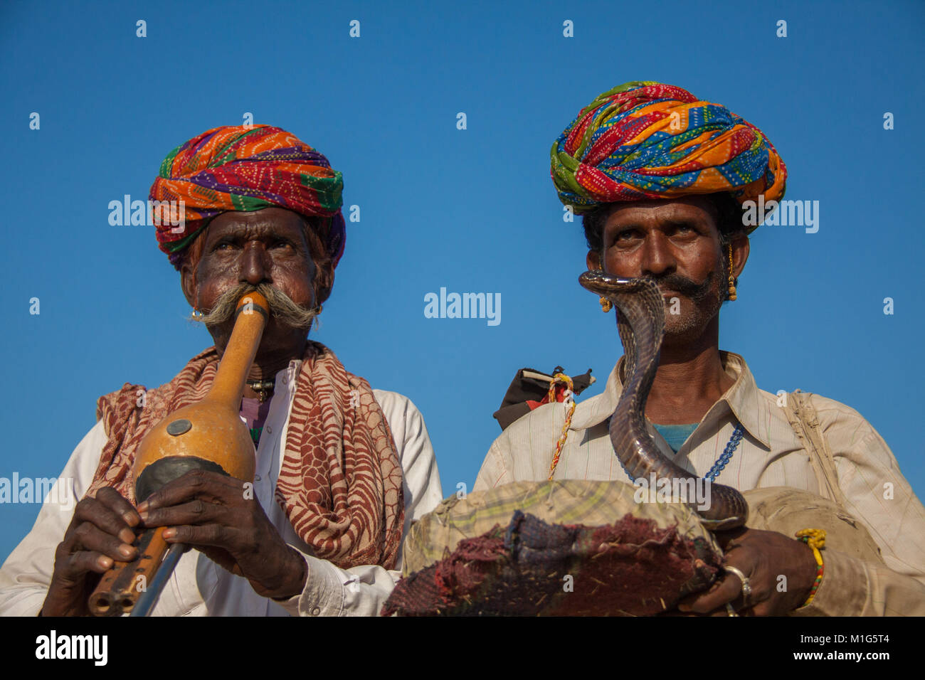Snake charmers with a cobra to entertain tourists for money at the Pushkar Camel Fair, Rajasthan, India - Stock Image
