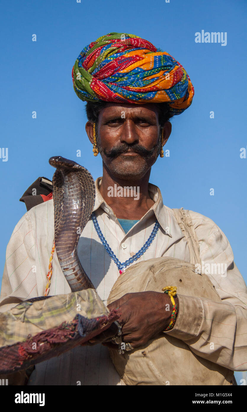 Snake charmer with a cobra to entertain tourists for money at the Pushkar Camel Fair, Rajasthan, India - Stock Image