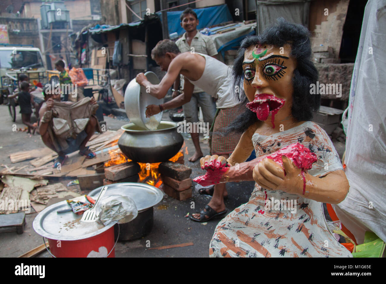 Calcutta / Kolkata street with food vendors next to a gruesome papier mache female model eating what looks like - Stock Image