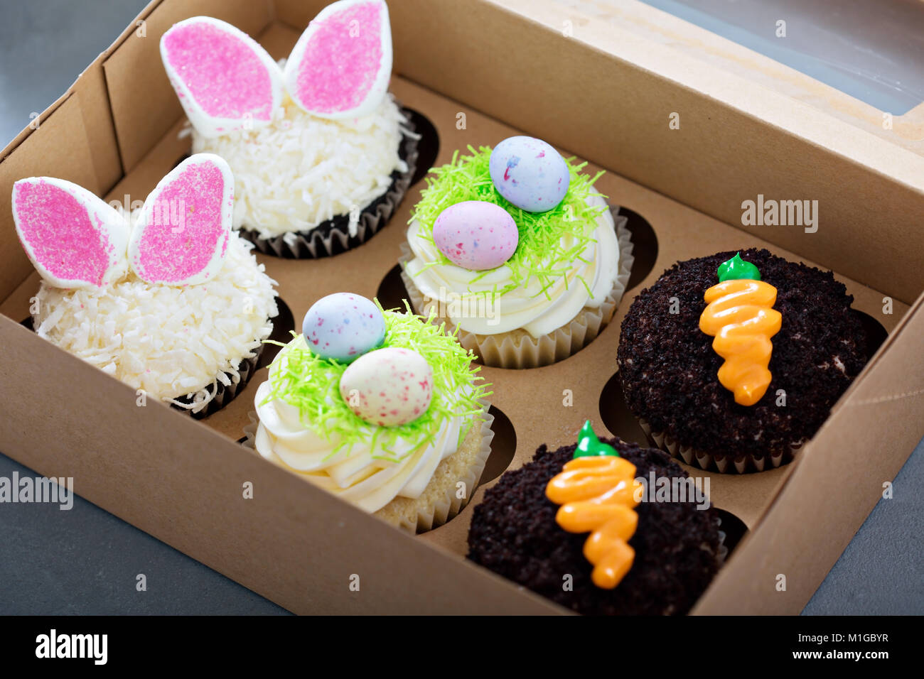 Assortment of easter cupcakes in a box with bunny ears and candy eggs - Stock Image