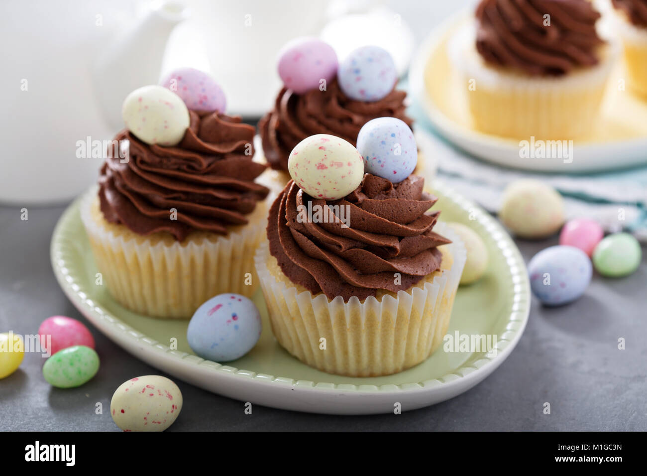 Easter vanilla cupcakes with chocolate frosting and candy eggs - Stock Image