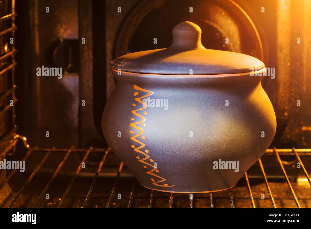 cooking soup - closed ceramic pot with stewed meat in electric oven - Stock Image