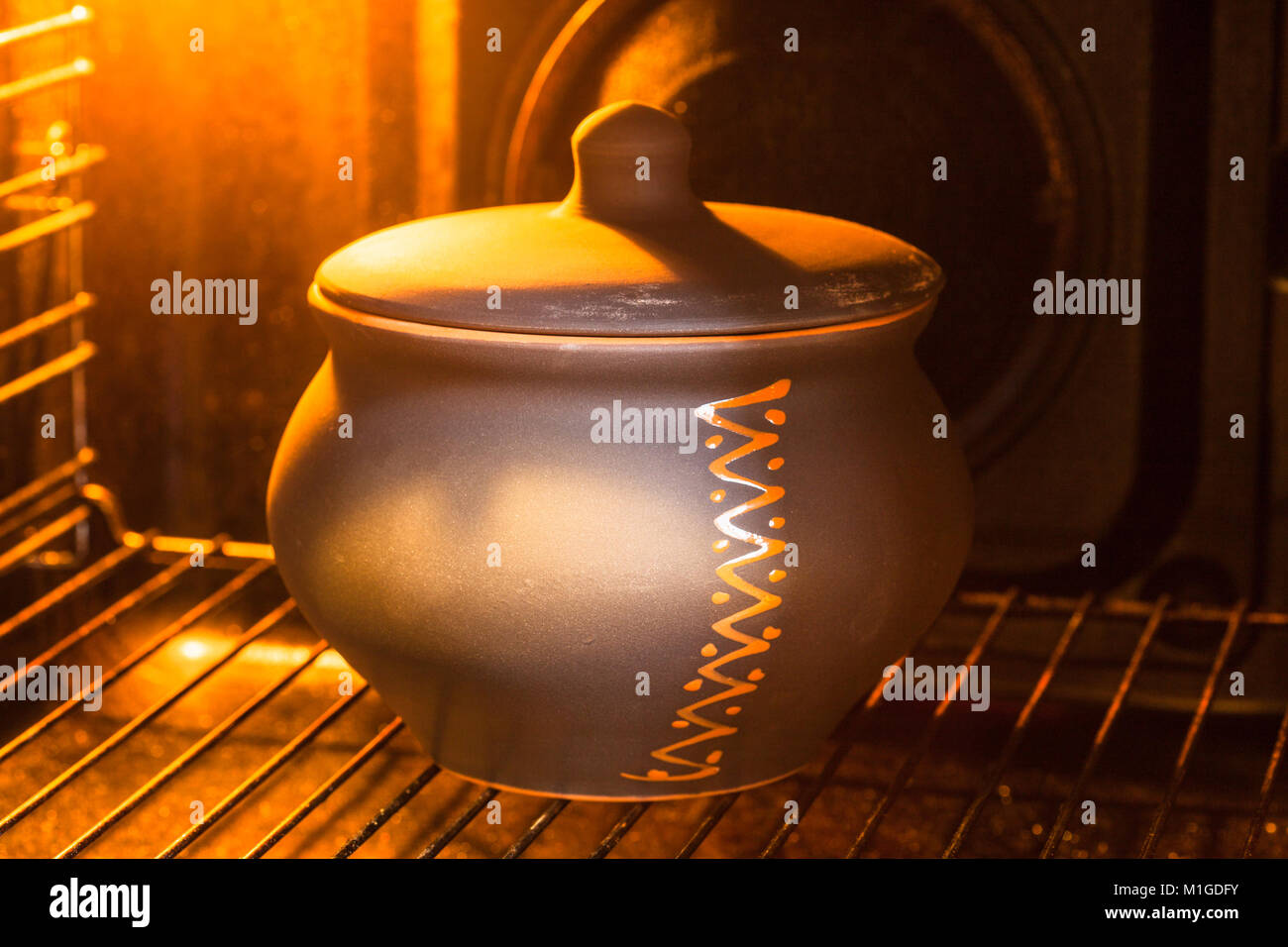 cooking soup - closed ceramic pot with stewed vegetables in hot electric oven - Stock Image