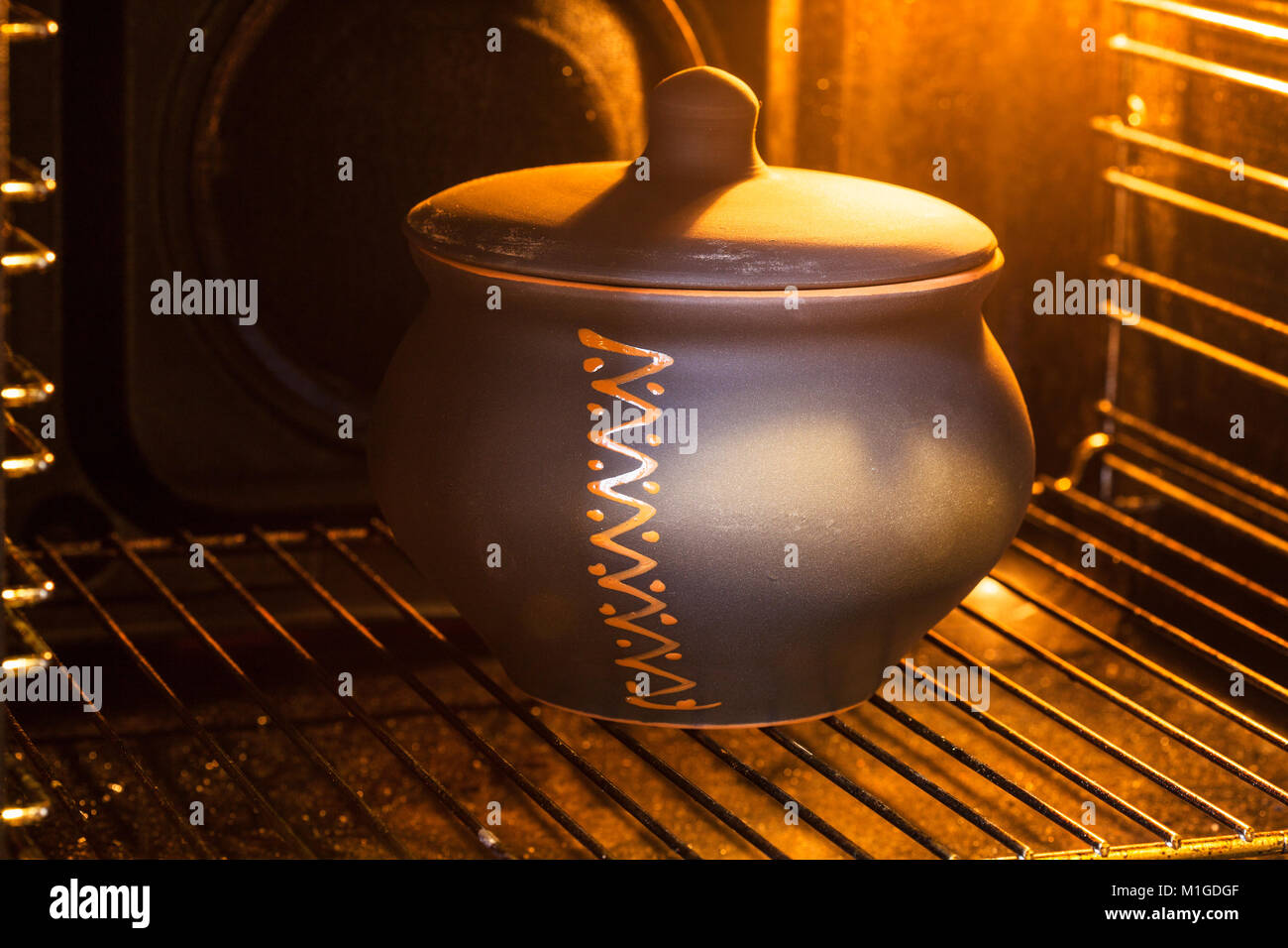 cooking soup - closed ceramic pot with stewed cabbage in illuminated electric oven - Stock Image
