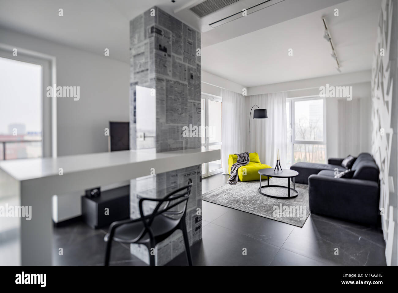 Black and white home interior with bright green chair Stock Photo