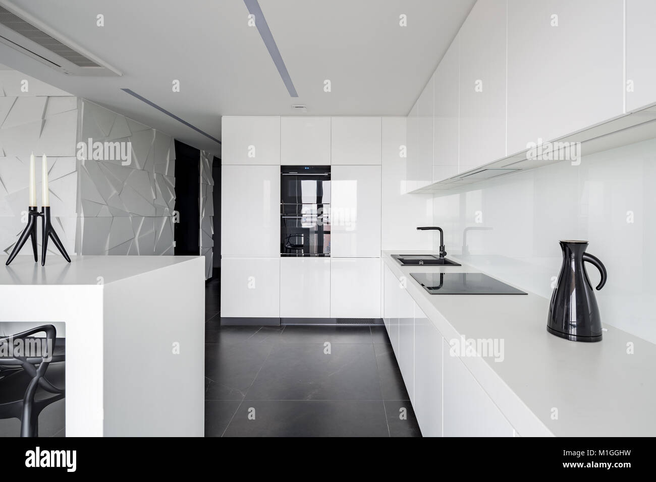 . High gloss white kitchen with modern equipment and black flooring