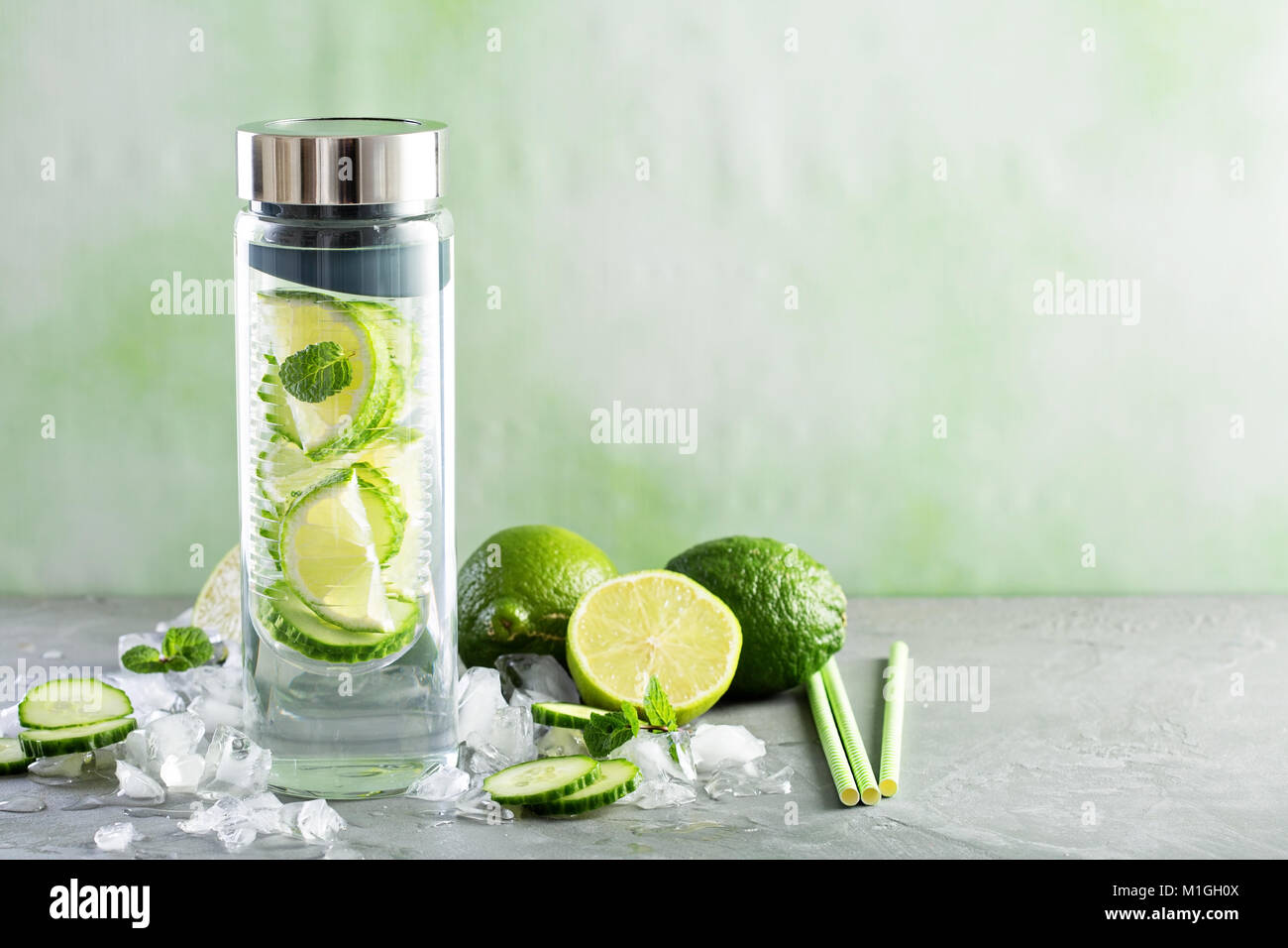 Infused water with lime and cucumber in a glass bottle - Stock Image