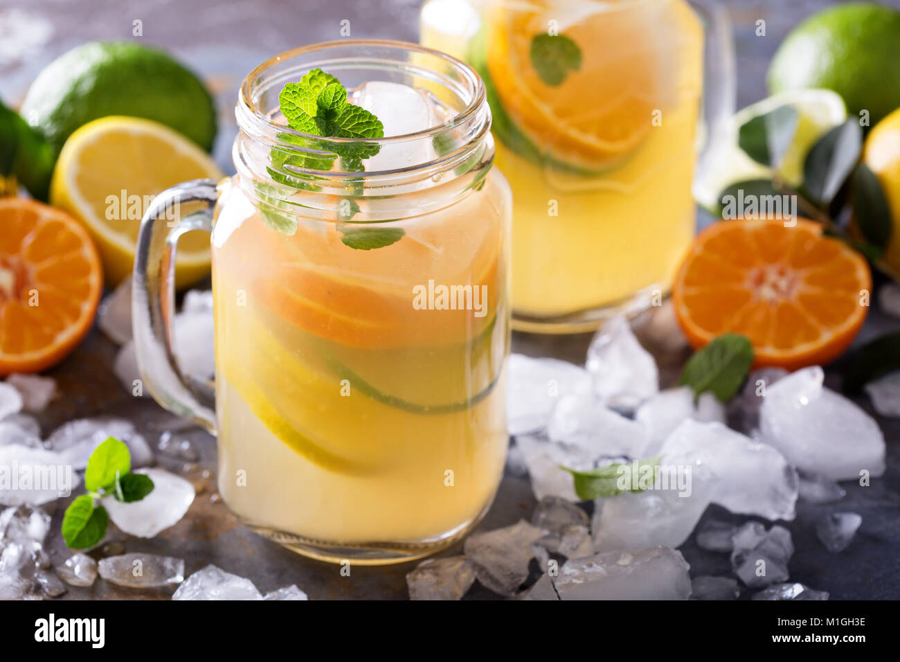 Citrus lemonade with slices of oranges, lemons and limes in mason jars - Stock Image