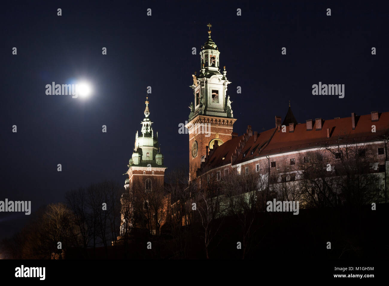 Towers of the Wawel Castle Cathedral Church in Krakow, Poland at night with full moon above - Stock Image