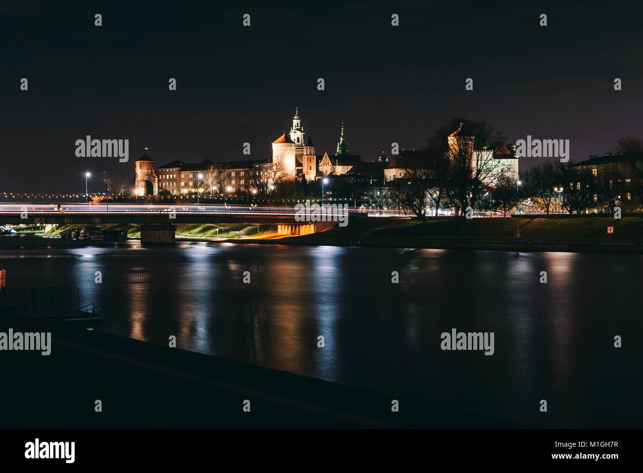 Wawel Castle in Krakow, Poland with Grunwaldzki bridge reflected in the river Vistula at night - Stock Image