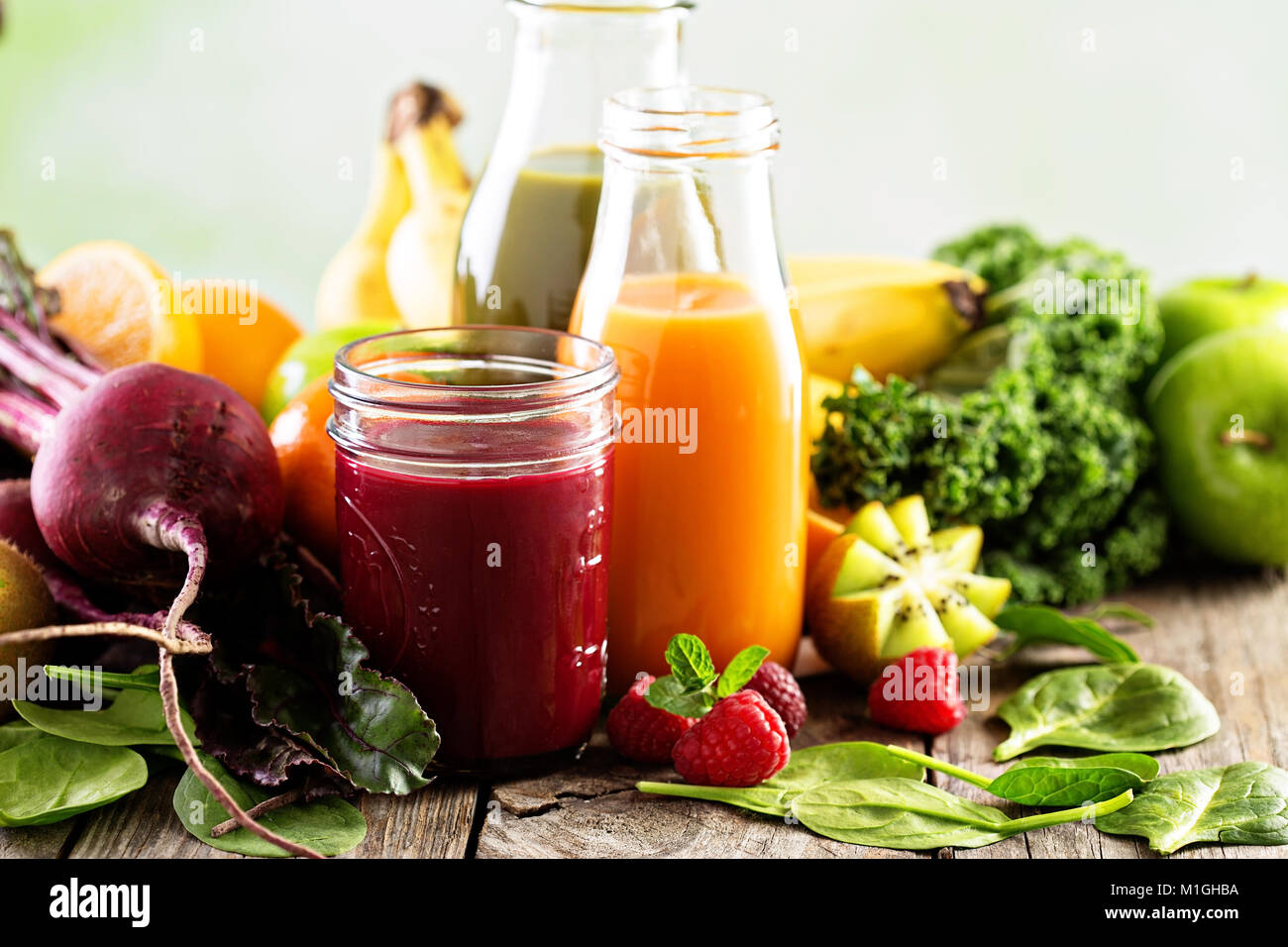 Fresh vegetable and fruit juices with beets, berries, oranges and greens - Stock Image