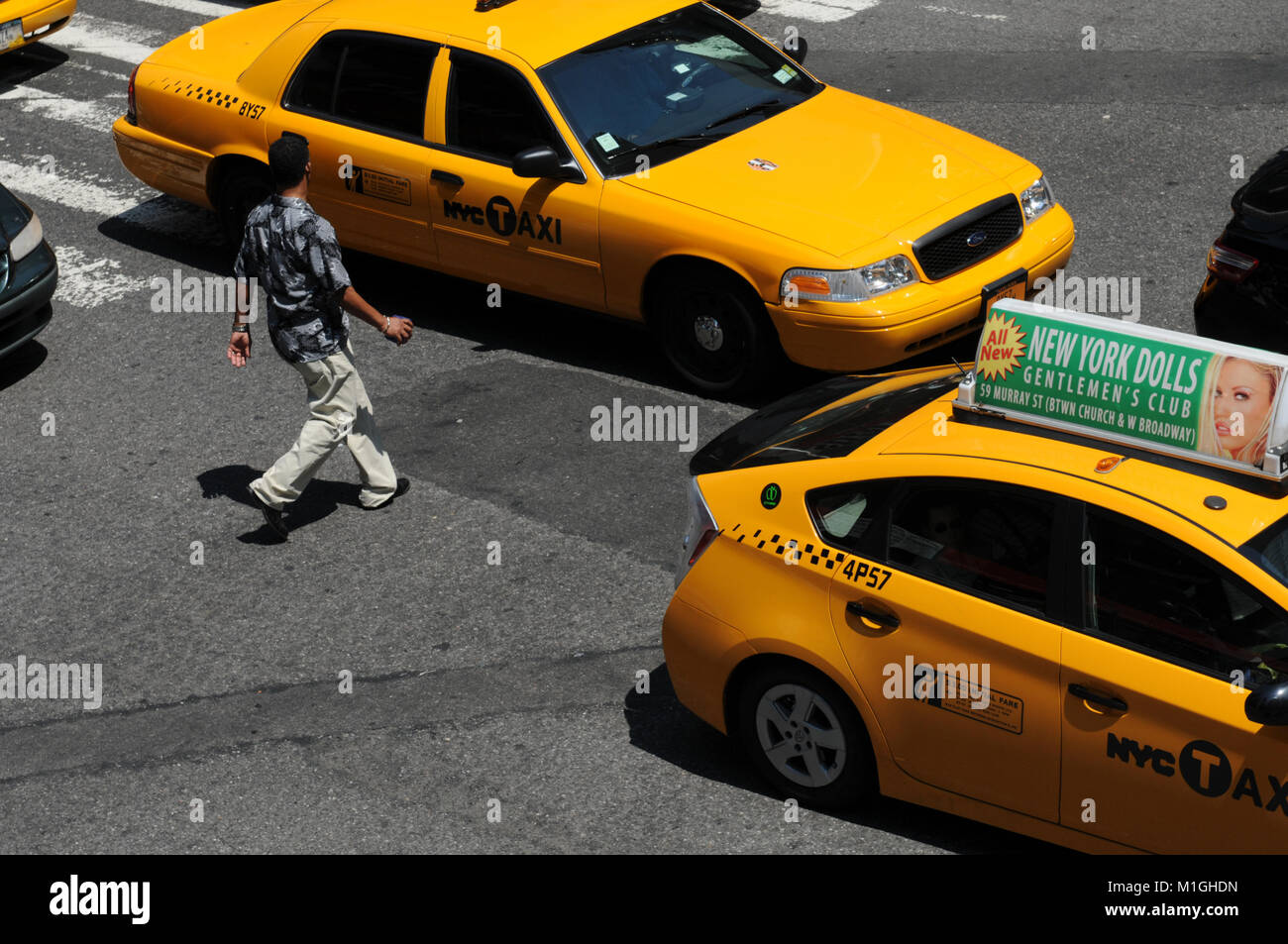 Man walking between yellow taxi cabs at the streets of New York City - Stock Image