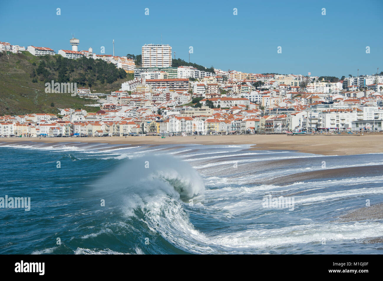 wave breaking onto the beach at Nazare, Portugal with the town in the background - Stock Image