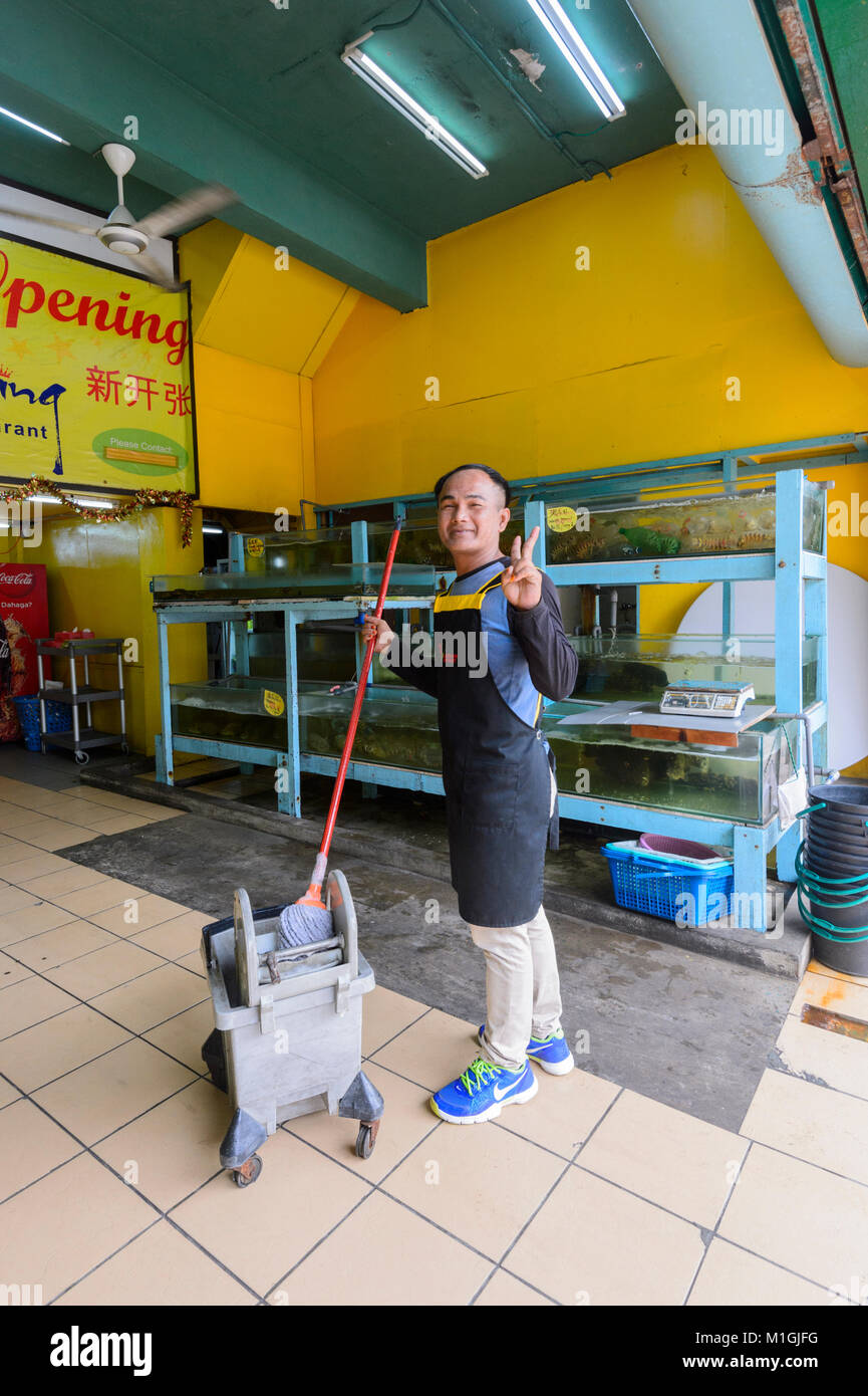 Smiling shop cleaner in town centre, Kota Kinabalu, Sabah, Borneo, Malaysia - Stock Image