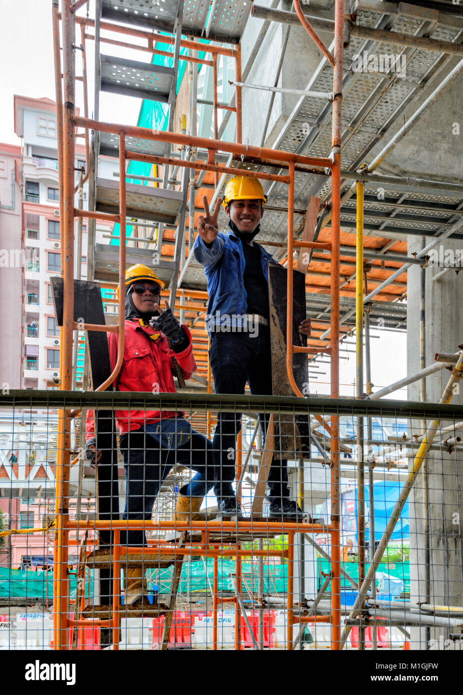 Workers on scaffoldings in town centre, Kota Kinabalu, Sabah, Borneo, Malaysia - Stock Image