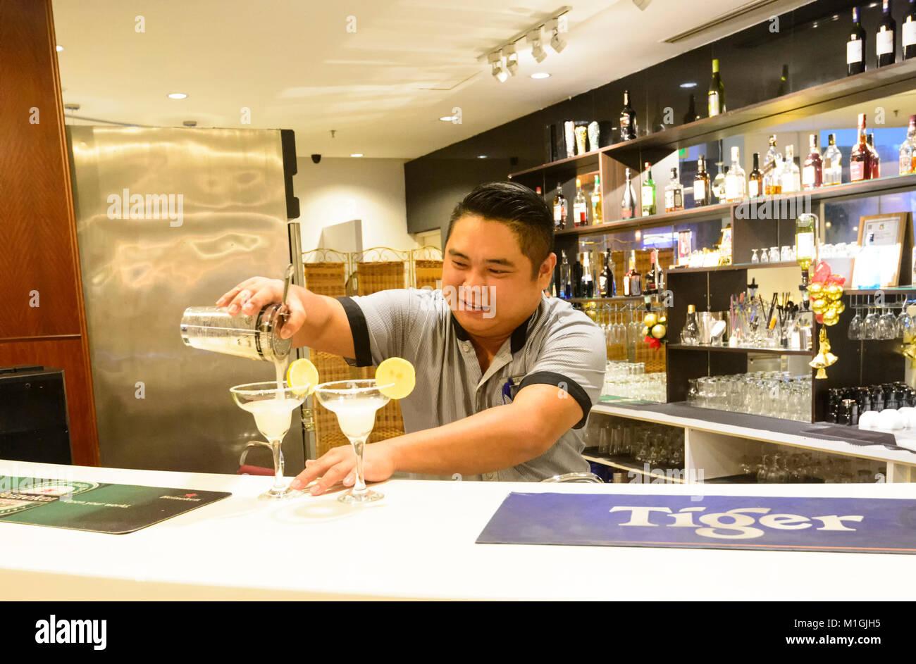 Barman serving cocktails at the Klagan Hotel bar, Kota Kinabalu, Sabah, Borneo, Malaysia - Stock Image