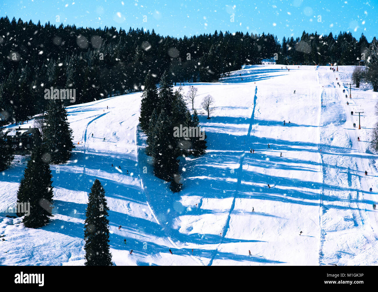 Piste ski tracks on snowy and sunny mountain side - Stock Image