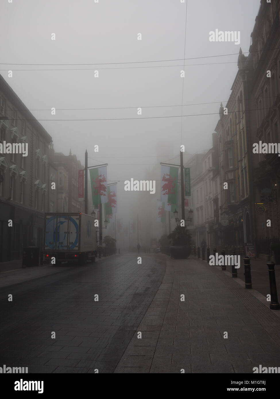 Commuters wend their way through the early morning fog on Cardiff's Mary Street, Wales - Stock Image
