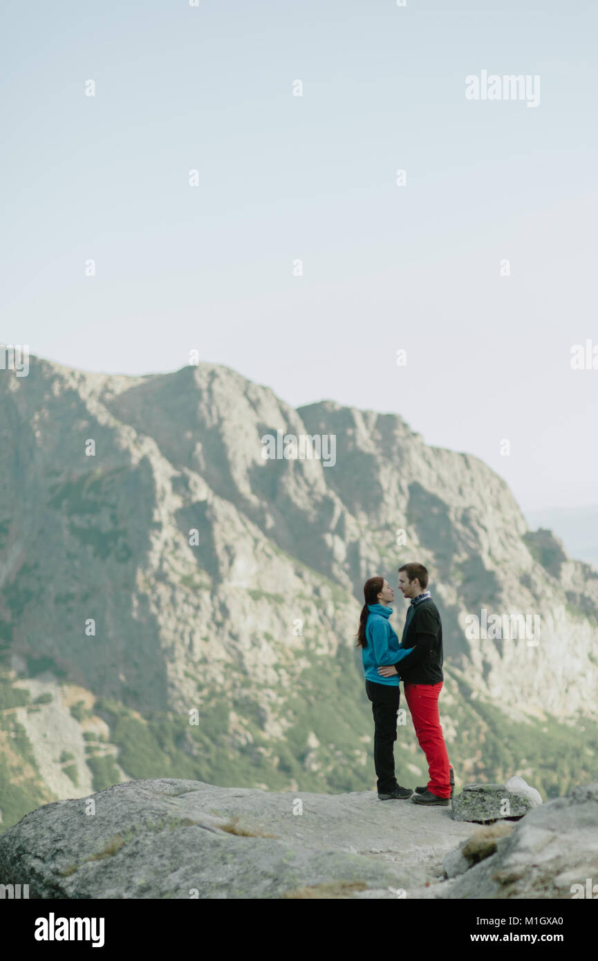 Man and woman in love hugging on top of mountains and looking into each other's eyes. - Stock Image