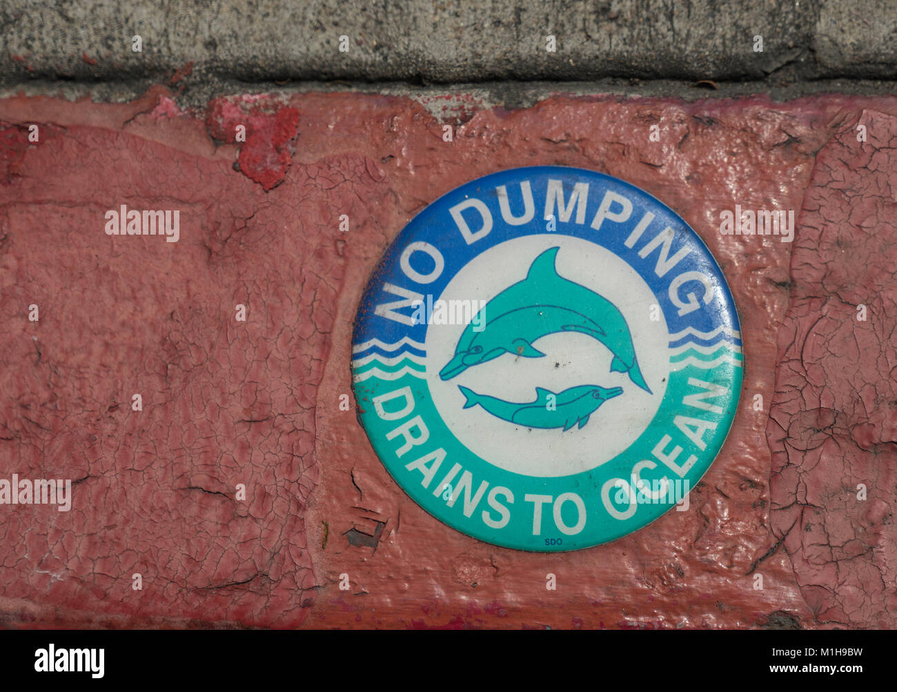 "Dolphin Sign On A Storm Drain In San Diego ""No Dumping Drains To Ocean"" Keep The Oceans Clean - Stock Image"