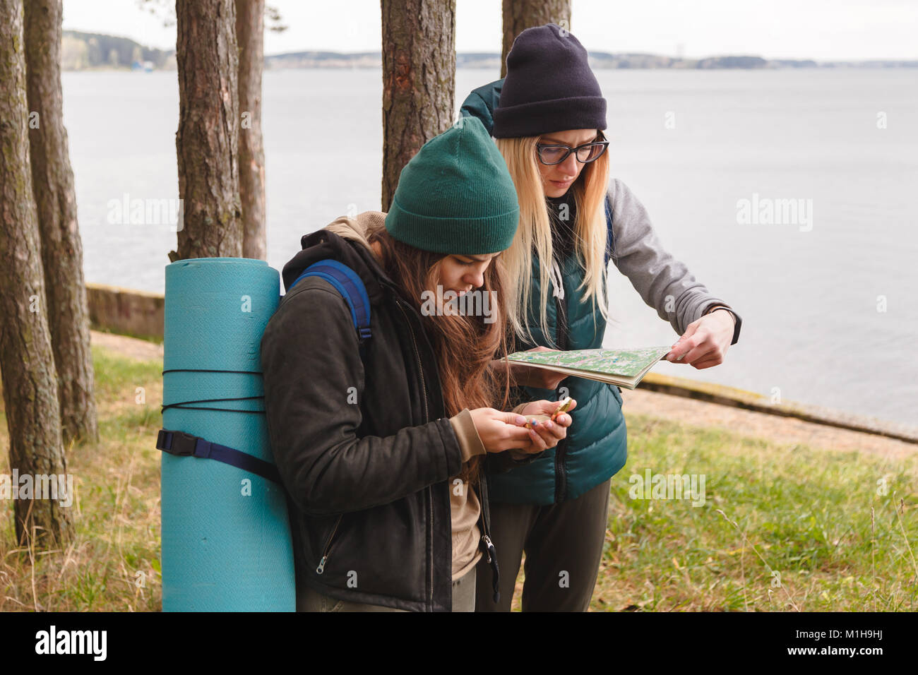 Two young tourist determine the route map and compass. - Stock Image