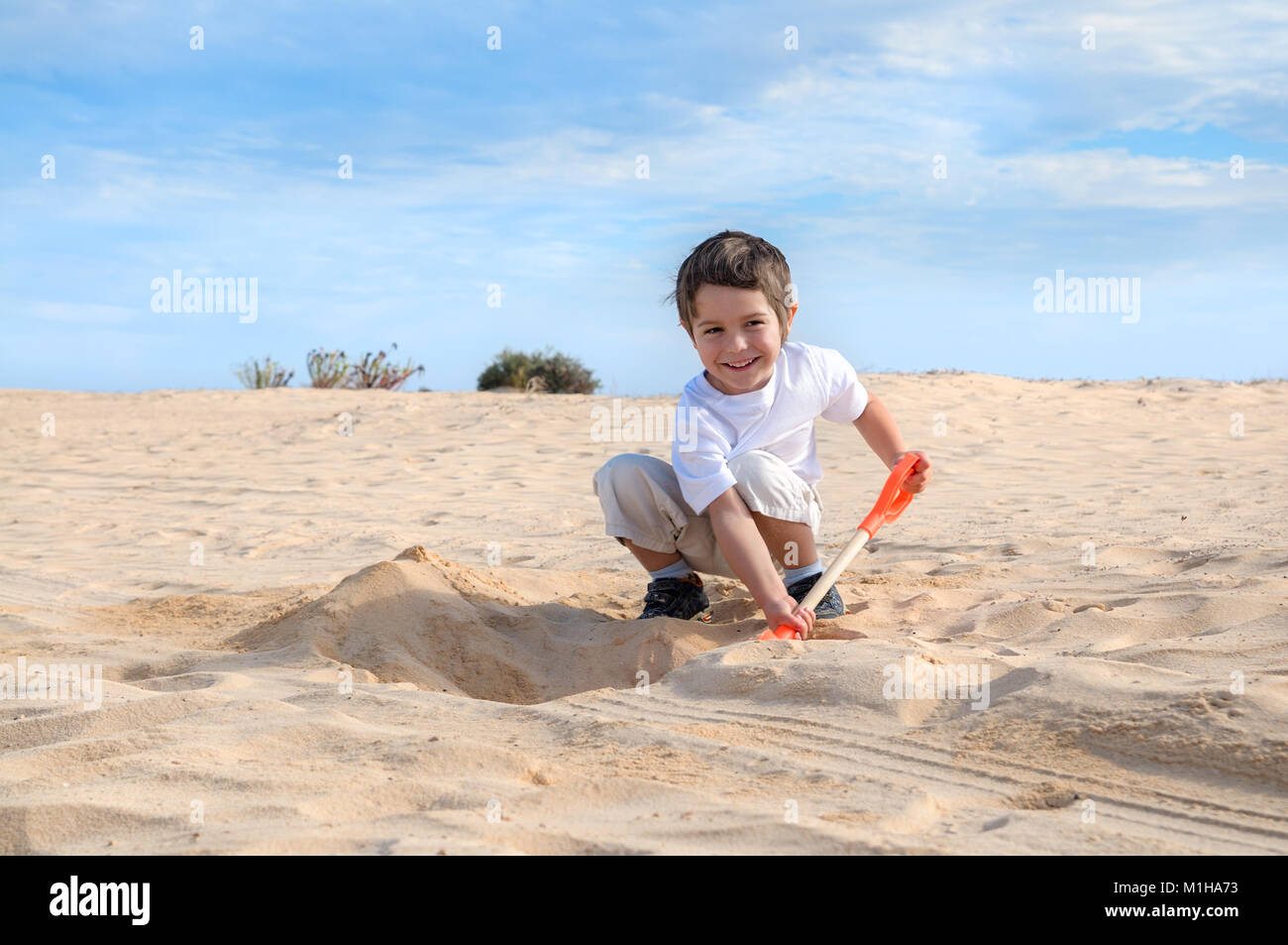 f7ce55c7c Smiling little boy in white t-shirt digs sand on a beach with orange showel