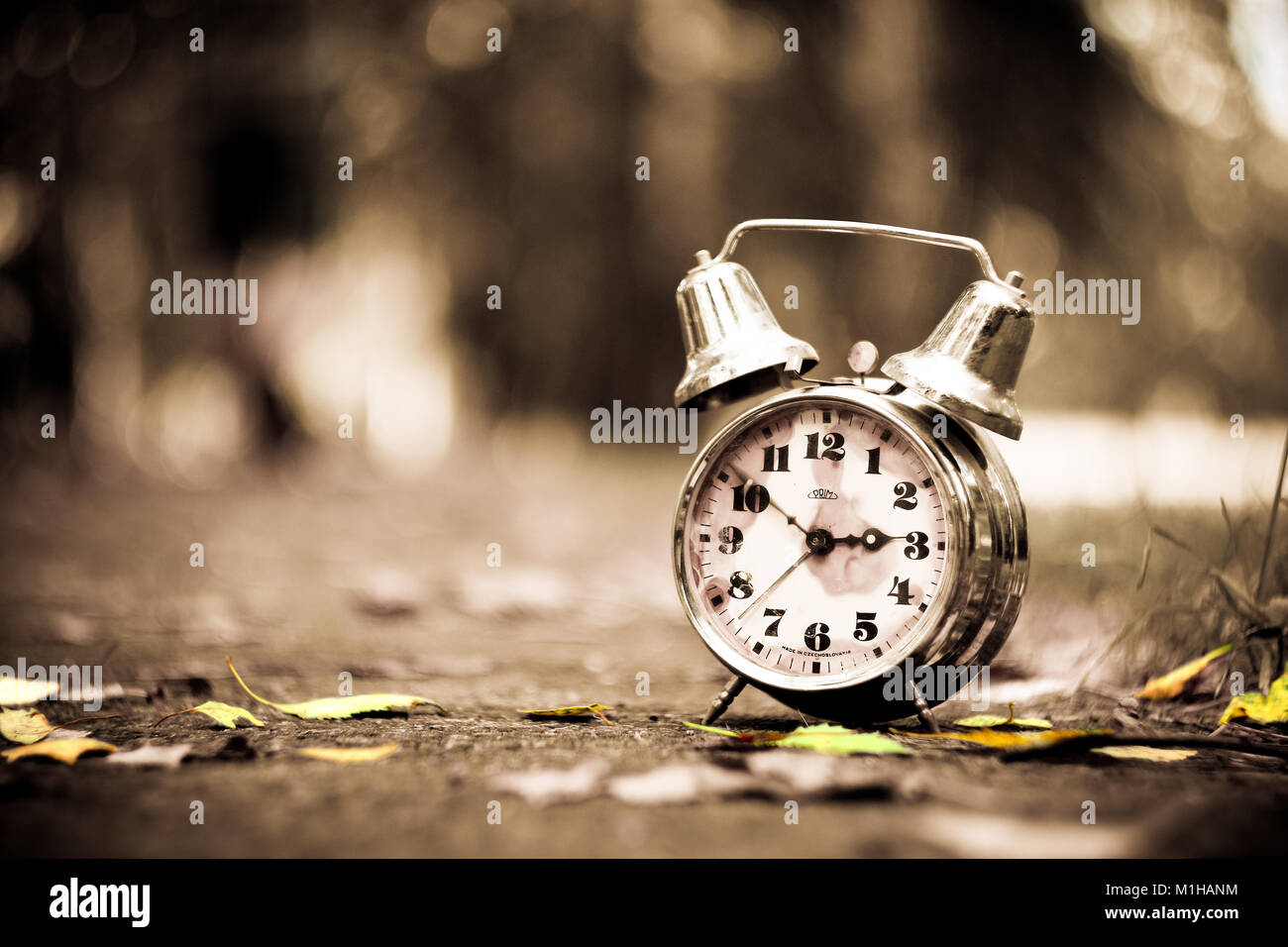 A vintage, little bit rusty, alarm clock standing on a road in the nature. The hands are moving. - Stock Image
