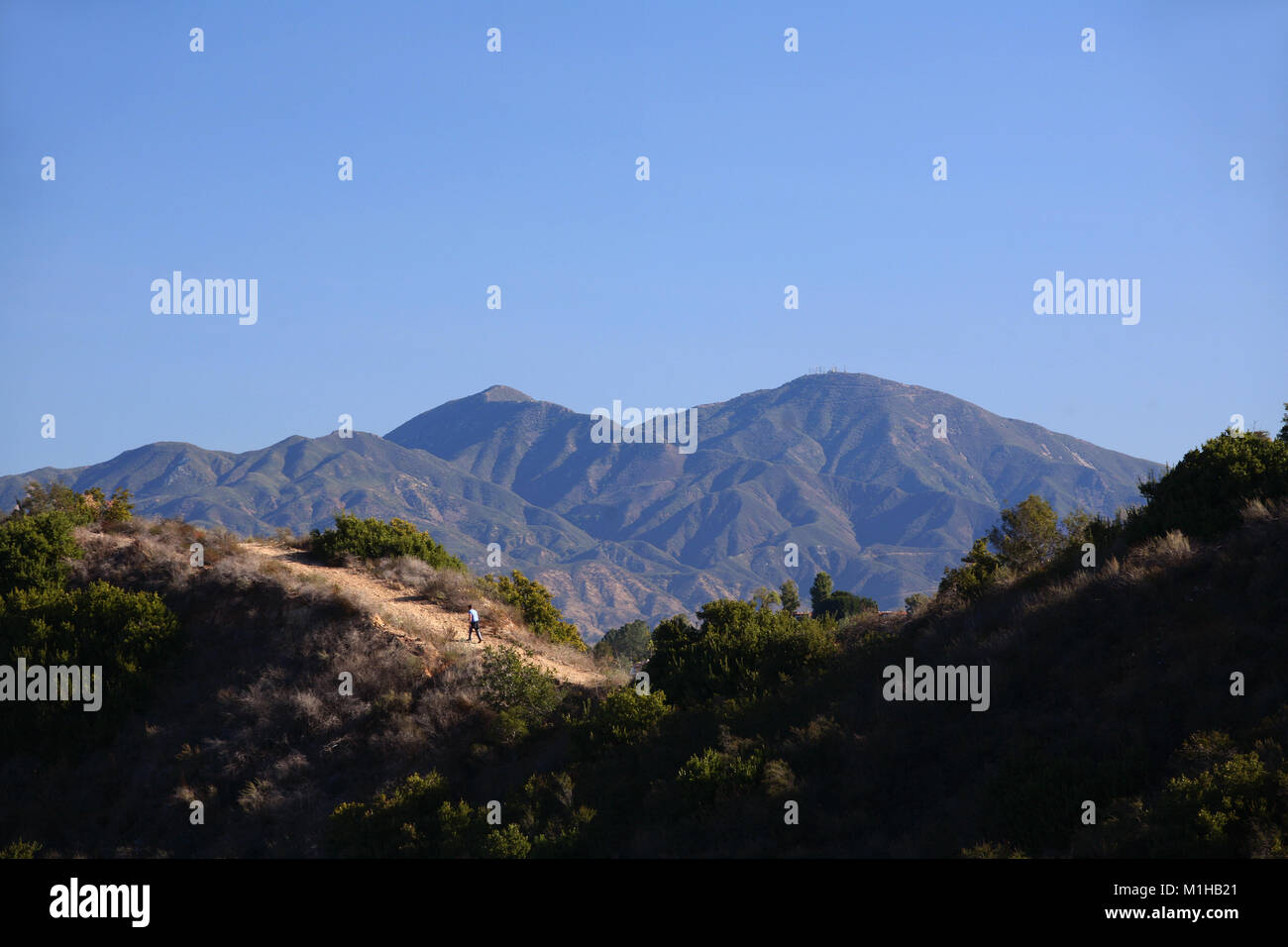 Hiker on trail in James Dilley Greenbelt preserve with view of Saddleback mountains Laguna Beach California - Stock Image