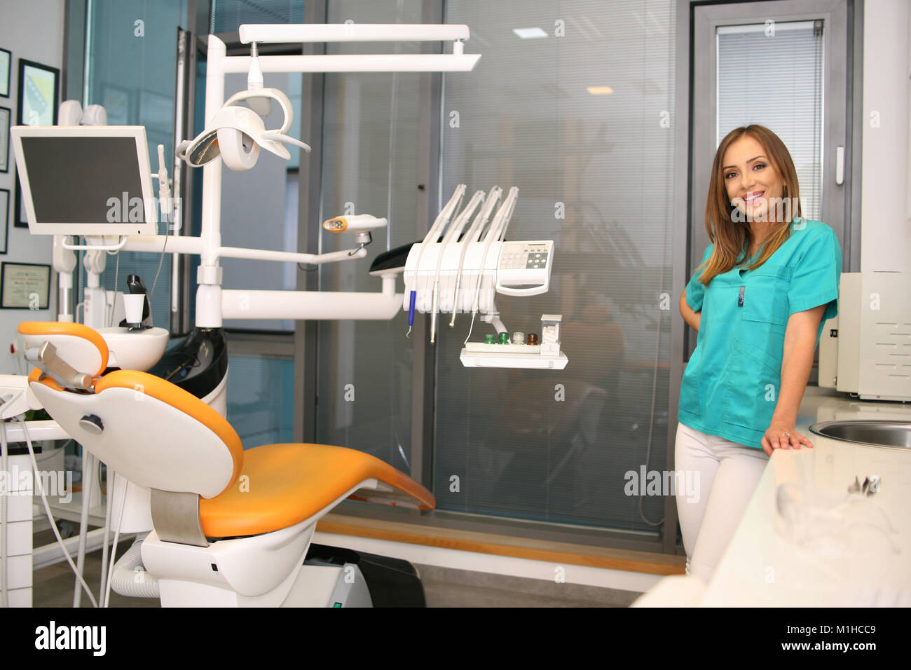 A young female dentist standing in her office, smiling into camera... - Stock Image