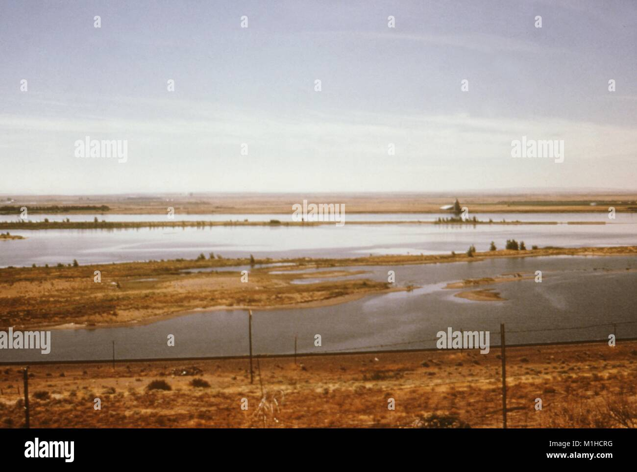 Photograph of a landscape consisting of a river with heaps of land and blue sky above, at the Umatilla Wildlife - Stock Image