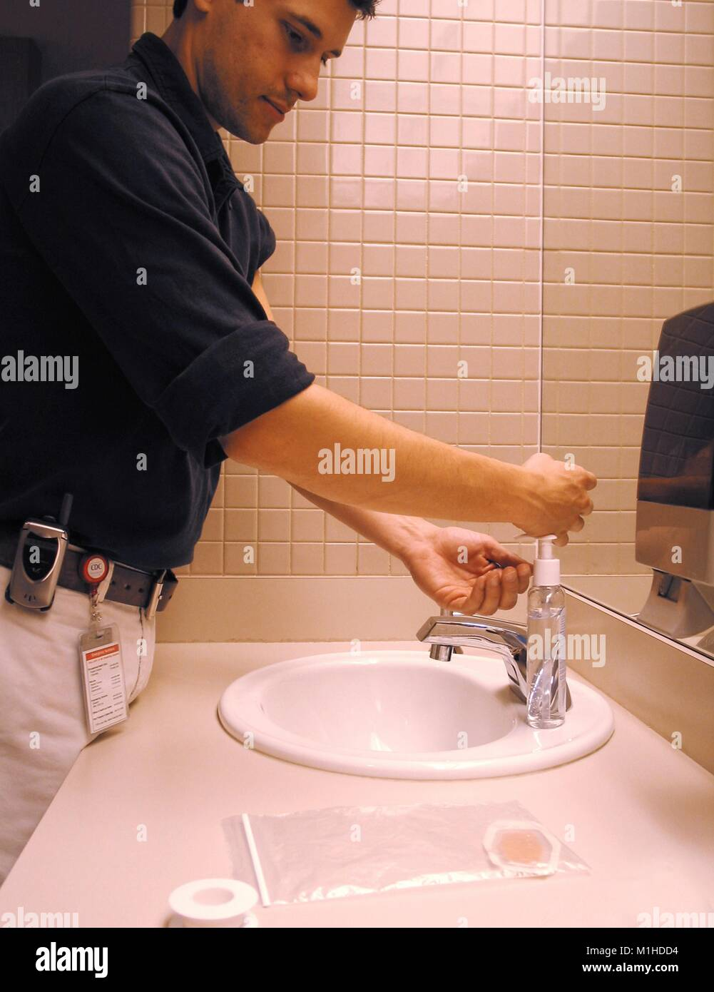 A picture of a man washing his hands with soap after receiving a smallpox vaccination, as part of the hygiene protocol - Stock Image