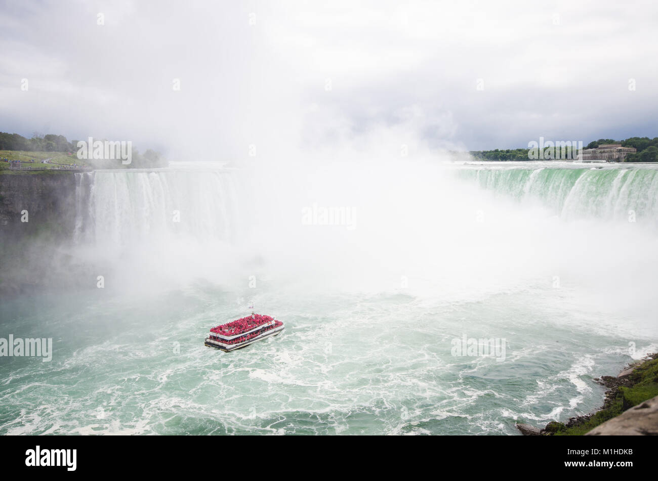 A boat full of tourists wearing red ponchos move into niagara falls through the mist - Stock Image