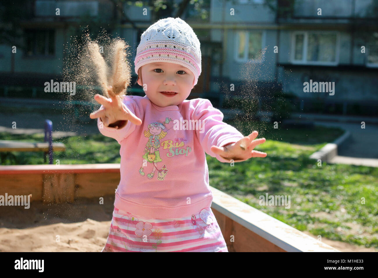 small child playing in the backyard and in the sandbox - Stock Image