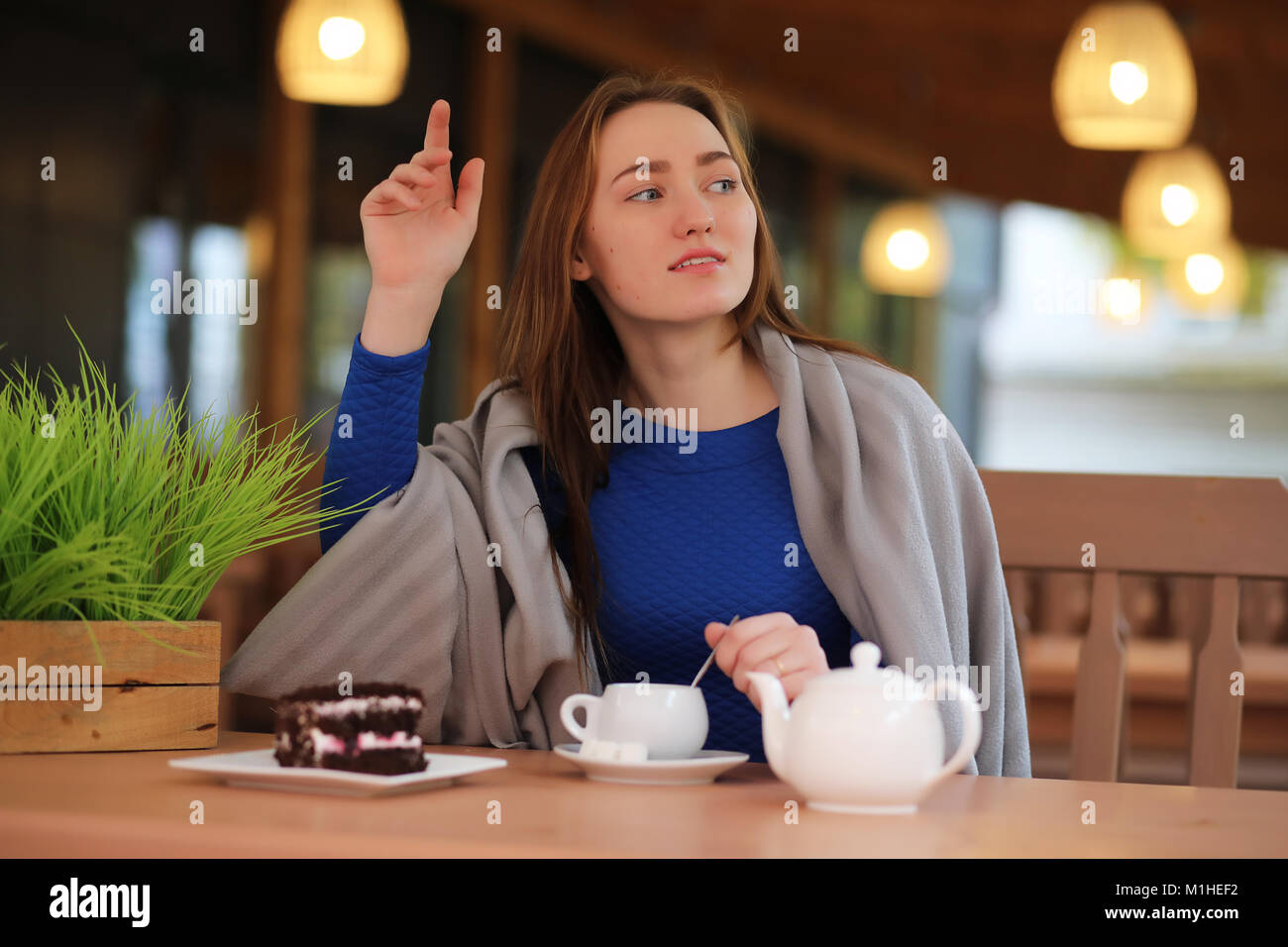 Young girl in cafe sits and drinks tea - Stock Image