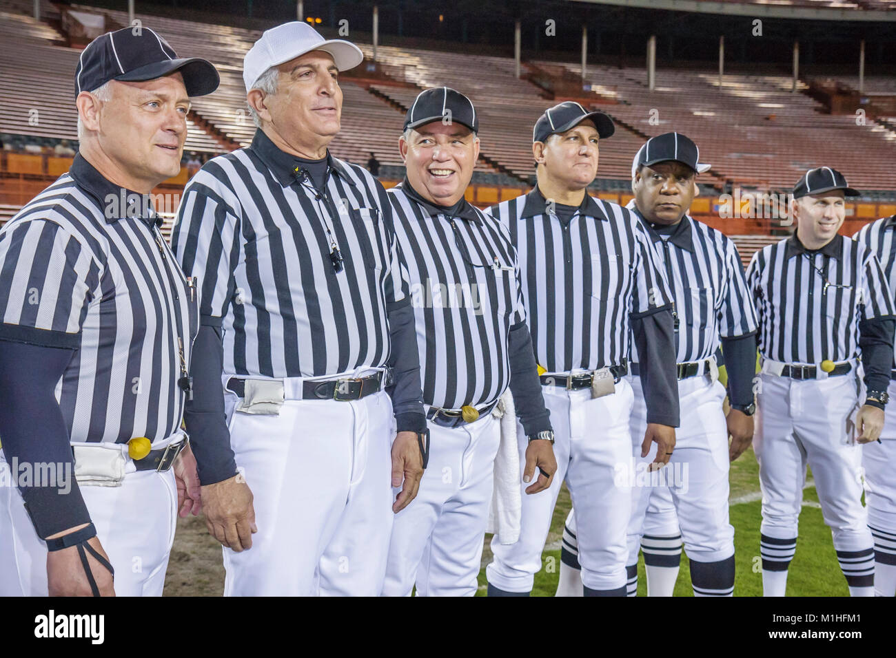 All American Offense Defense Bowl high school football referees officials striped uniforms Black man men - Stock Image