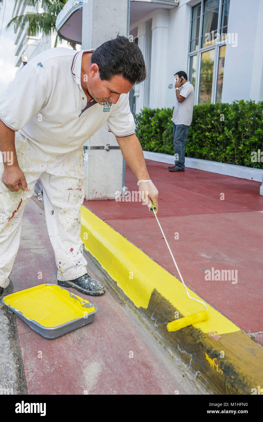 Miami Beach Florida Ocean Drive Savoy Hotel Hispanic man worker paints curb yellow maintenance job - Stock Image